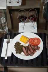 pan-seared flank steak, sautéed spinach, corn on the cob, and sliced tomatoes